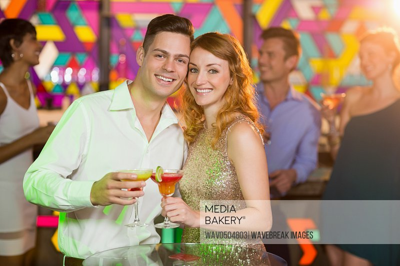 Portrait of romantic couple having glass of cocktail in bar