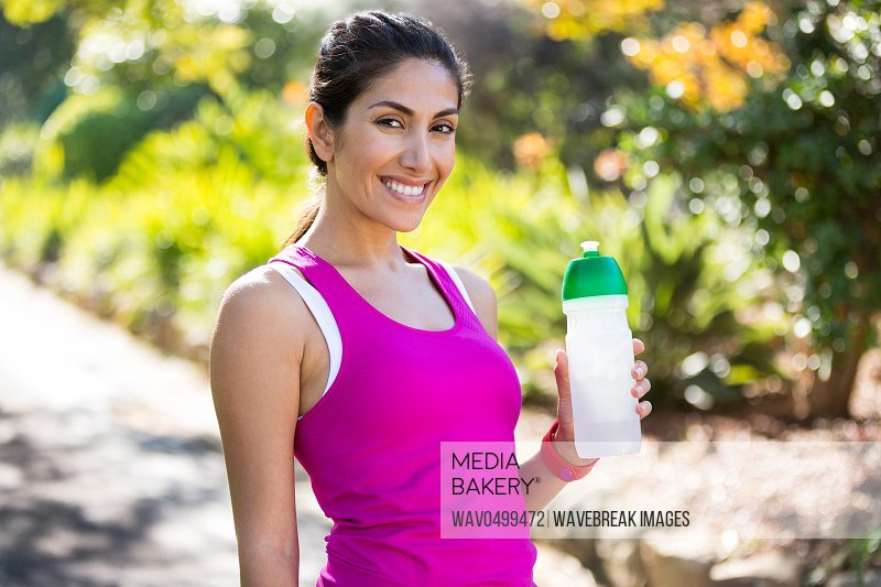 Portrait of smiling jogger drinking water while taking a break in park
