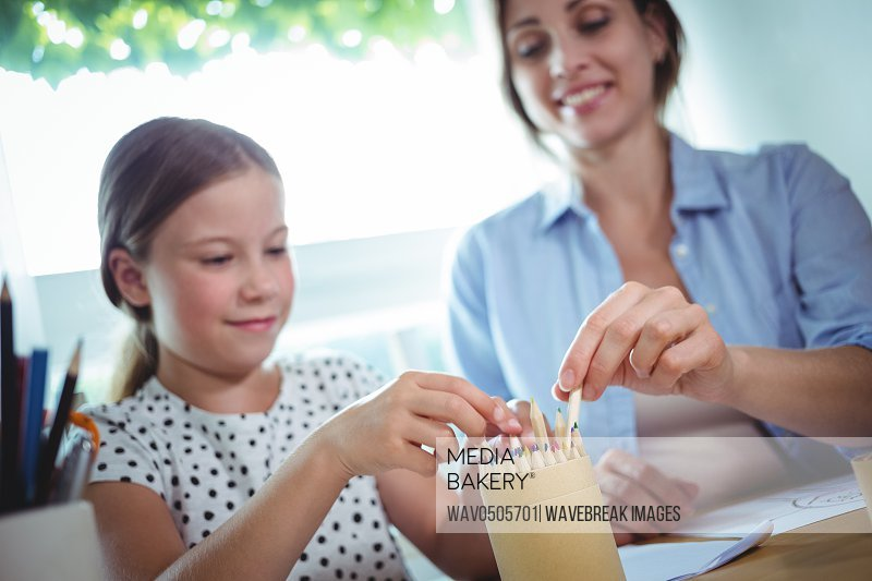 Smiling daughter and mother removing color pens from the box