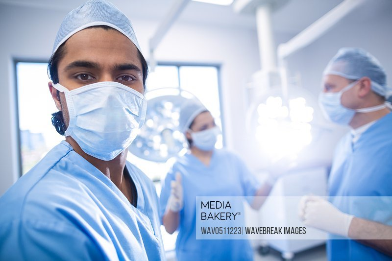 Portrait of male surgeon looking at camera while colleagues interacting in background in operation room