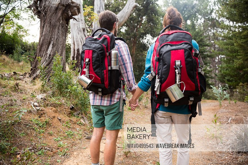 Rear view of hiker couple hiking in forest at countryside