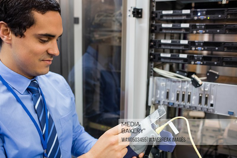 Technician using digital cable analyzer in server room