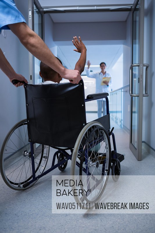 Boy sitting on wheelchair and waving hand to doctor in corridor at hospital