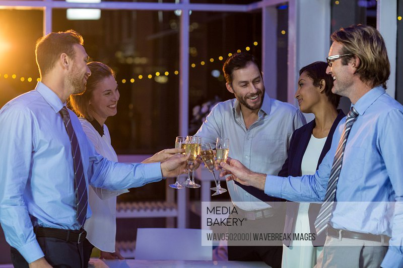 Businesspeople toasting glasses of champagne in office at night