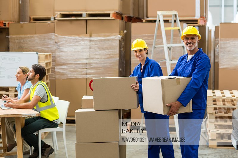 Portrait of delivery workers carrying cardboard box in warehouse