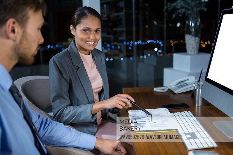 Business executives working on computer with graphic tablet in office at night