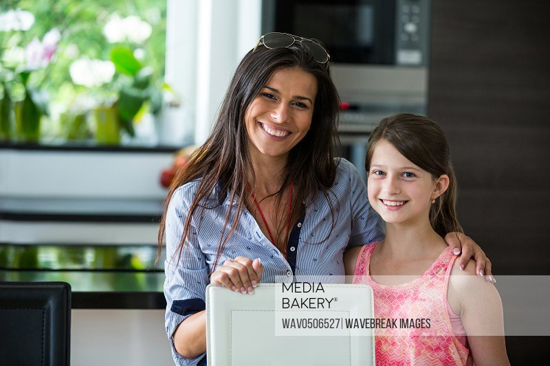 Portrait of mother and daughter together in living room at home