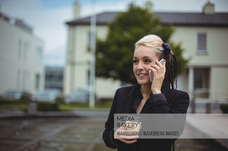 Businesswoman talking on mobile phone while holding disposable coffee cup in office campus