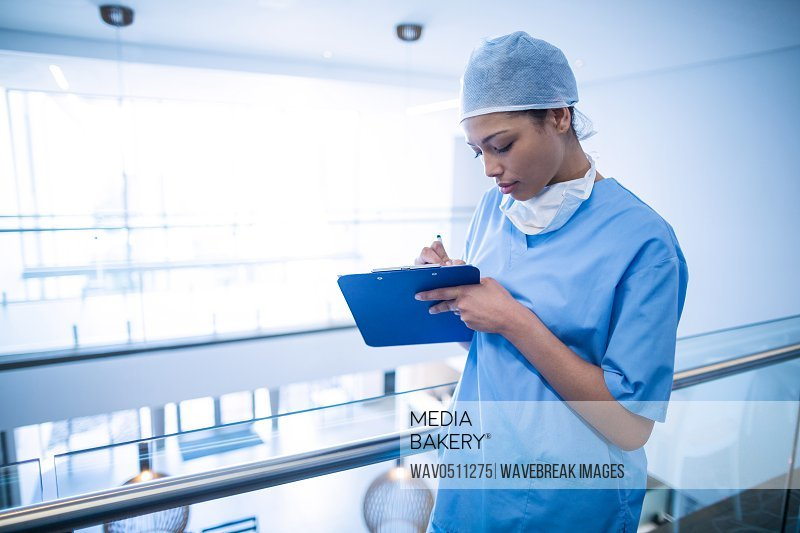 Female surgeon writing on a clipboard at hospital