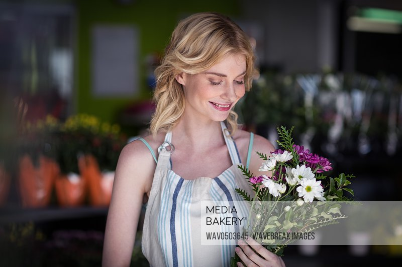 Happy female florist holding bunch of flowers in the shop