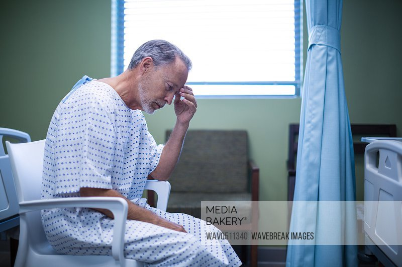 Sad patient sitting on chair with hand on head at hospital