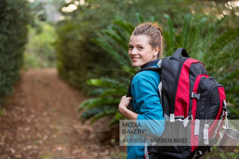Portrait of smiling female hiker standing in forest