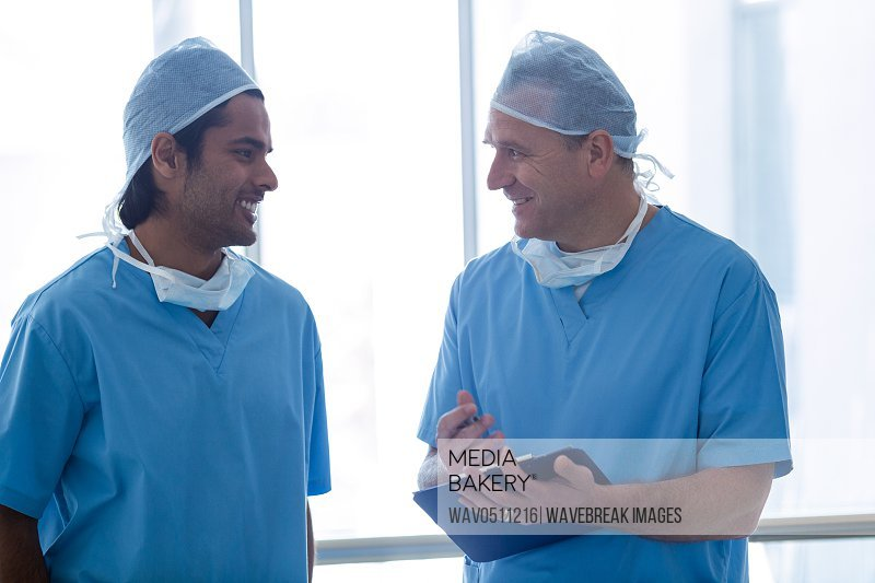 Surgeons discussing over medical reports in hospital corridor