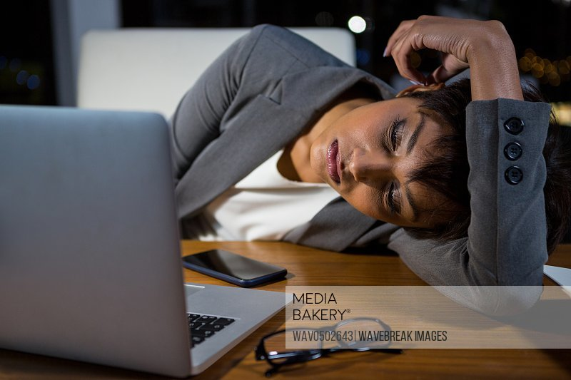Tired businesswoman sleeping on the desk in office at night