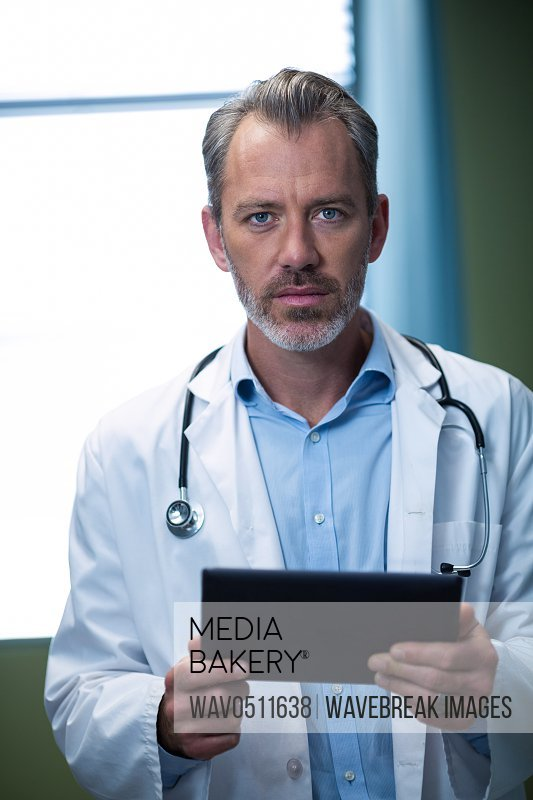 Portrait of doctor using digital tablet in ward of hospital