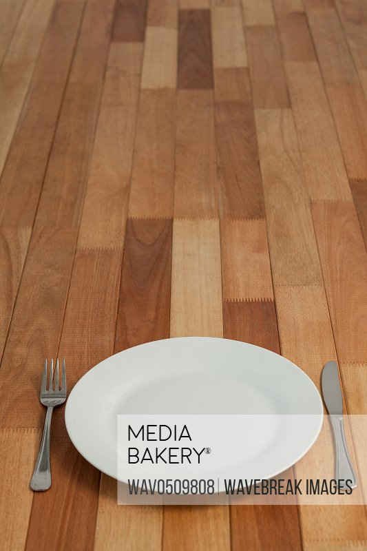 White empty plate, knife and fork served on wooden table