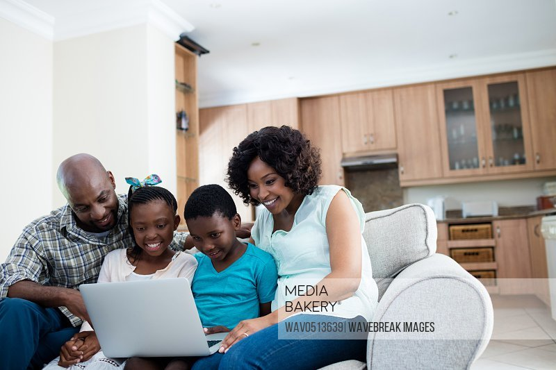 Parents and their children using laptop in living room