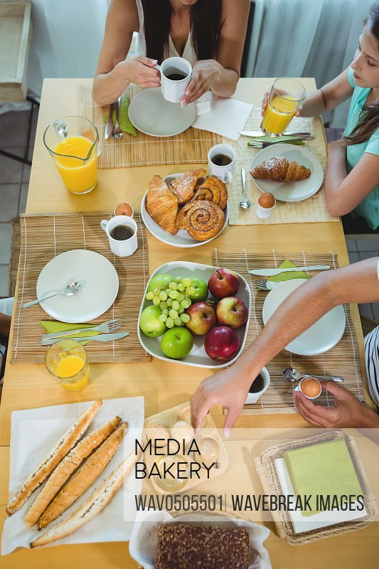 Overhead view of family sitting at breakfast table at home