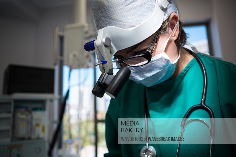 Surgeon wearing surgical loupes while operating in operation theater