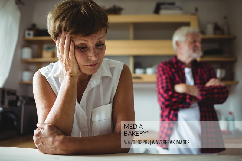 Worried senior woman leaning on table at home
