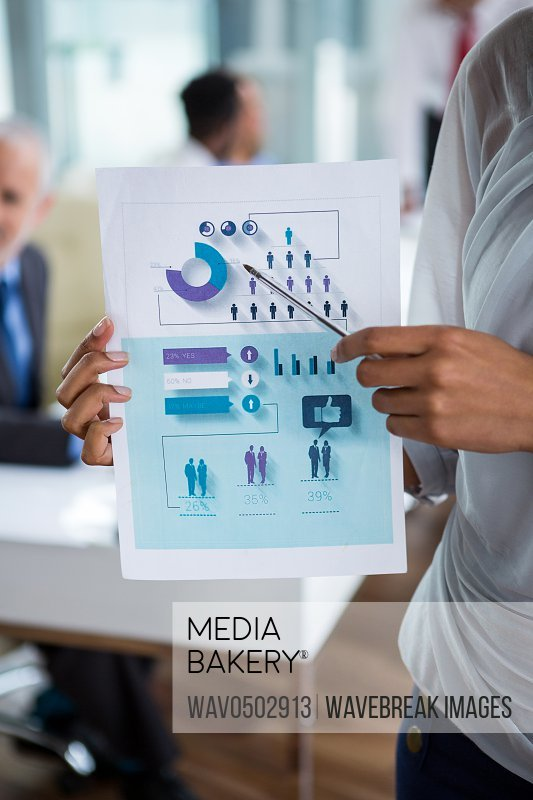 Mid section of businesswoman showing chart in office