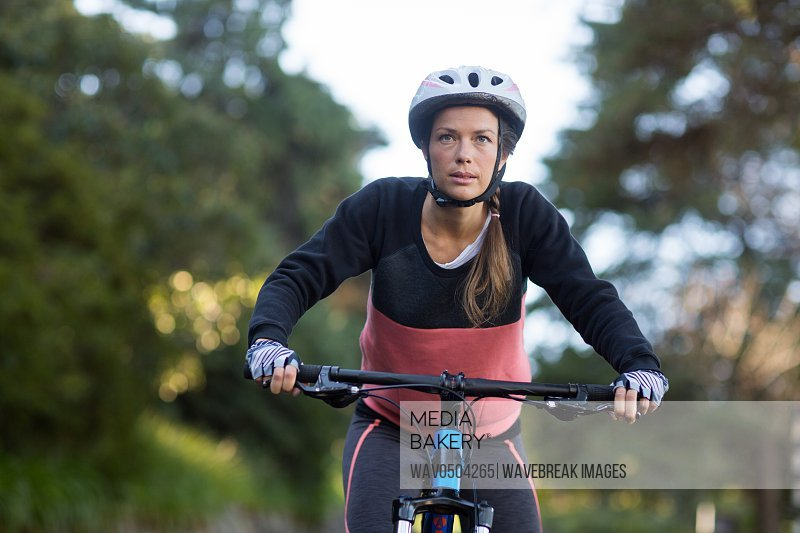 Female biker cycling in countryside on sunny day