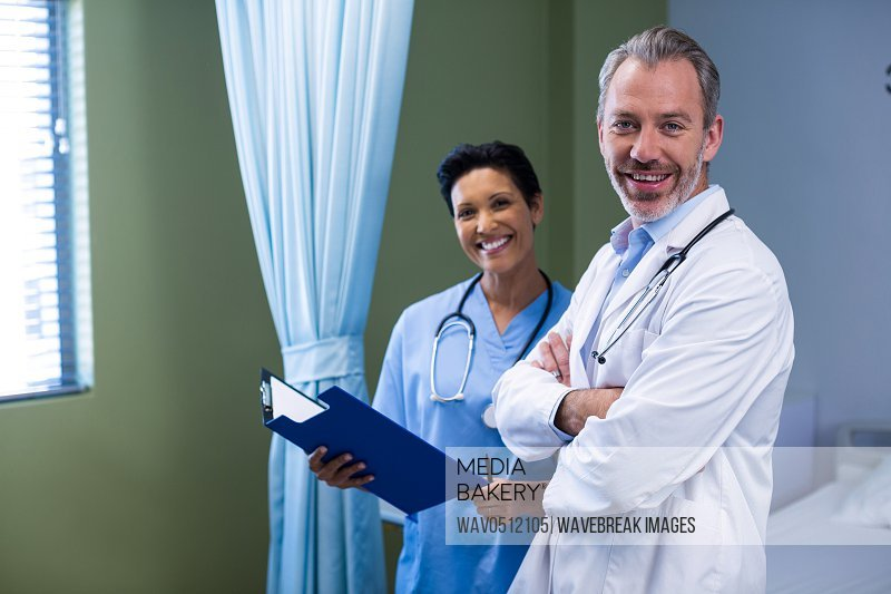 Portrait of doctor and nurse standing in ward of hospital
