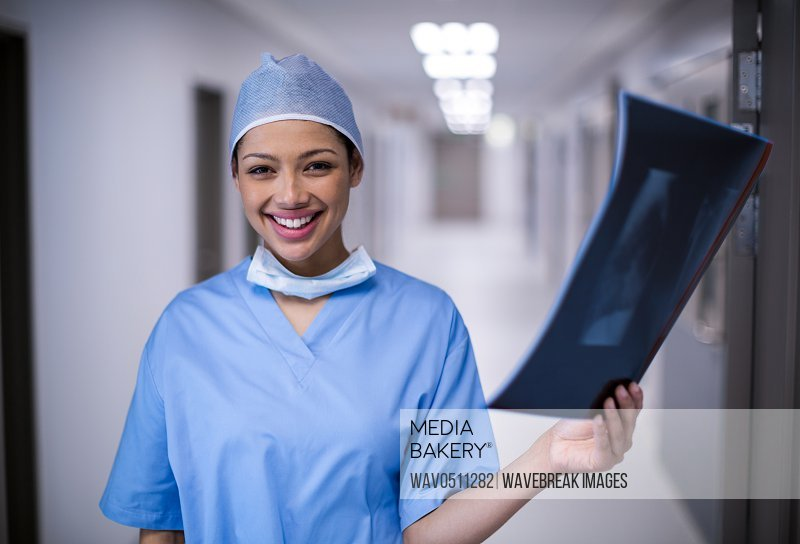 Portrait of female surgeon holding x-ray at hospital
