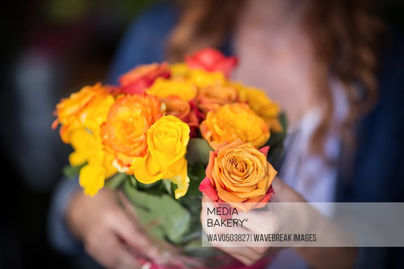 Female florist holding bunch of flowers in the shop
