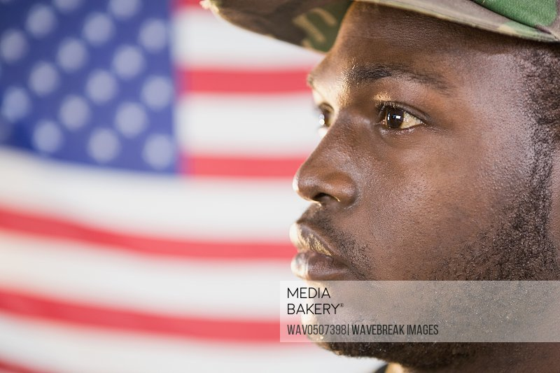 Close-up of confident soldier against american flag