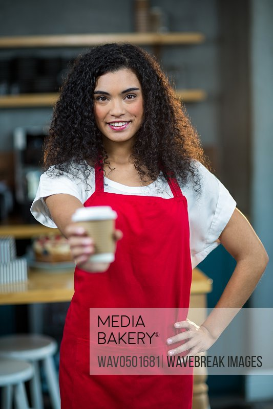 Portrait of waitress showing disposable cup of coffee