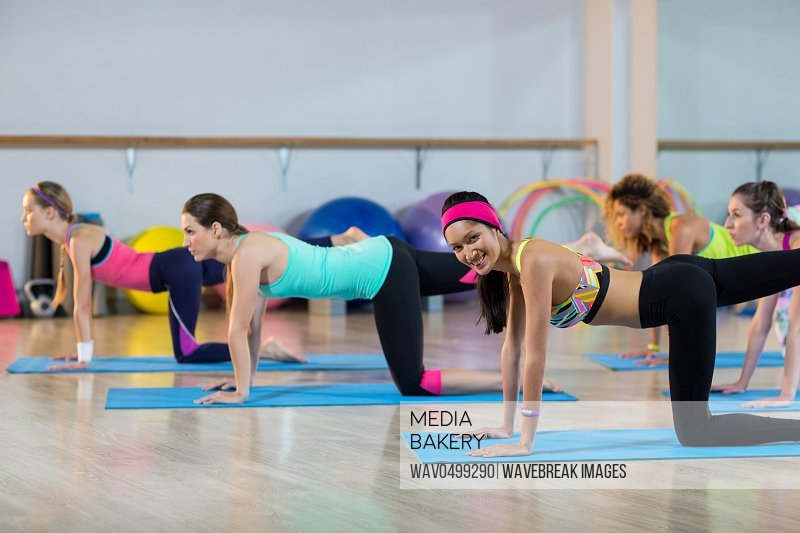 Group of women performing stretching exercise in gym