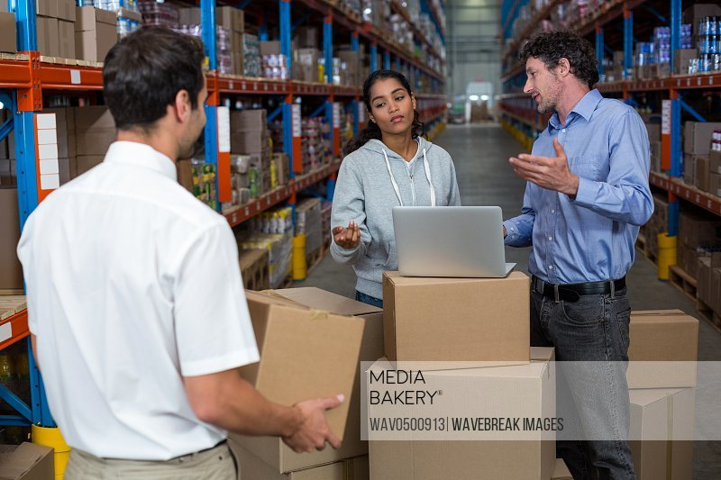 Warehouse manager carrying a box and his colleagues discussing in the warehouse