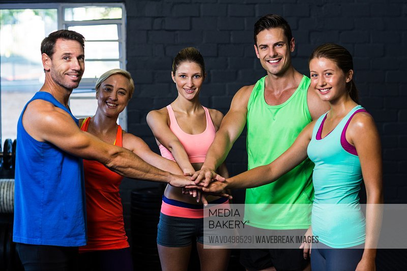 Portrait of cheerful friends putting hands together while standing in gym