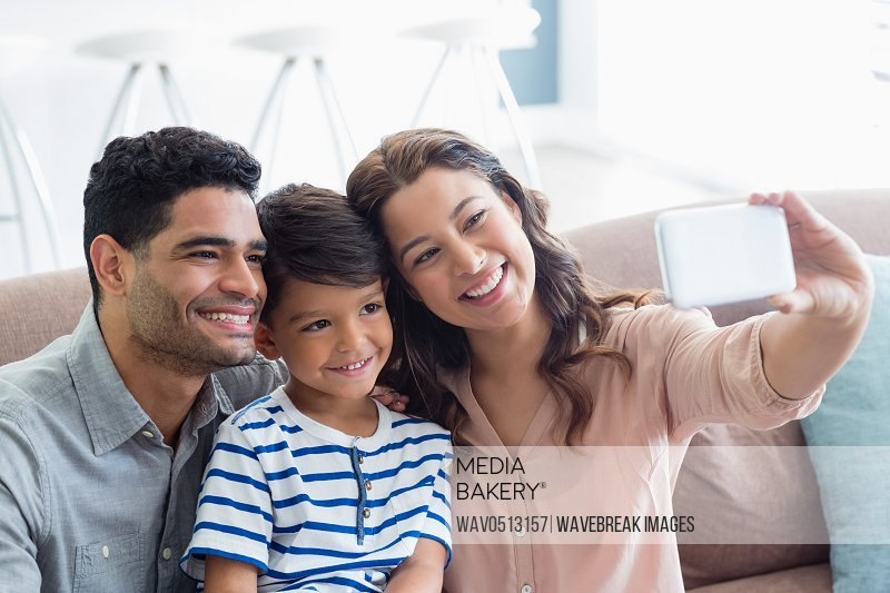 Parents and son taking a selfie from mobile phone in living room