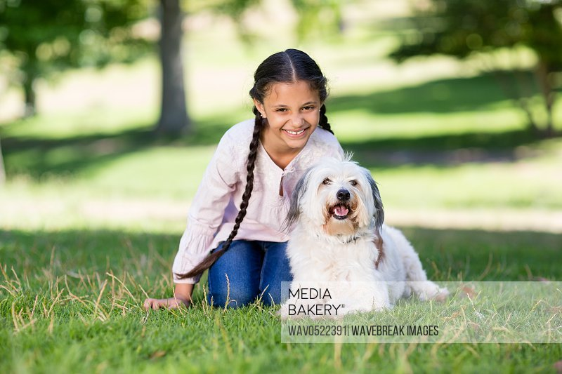 Portrait of smiling girl playing with her pet dog