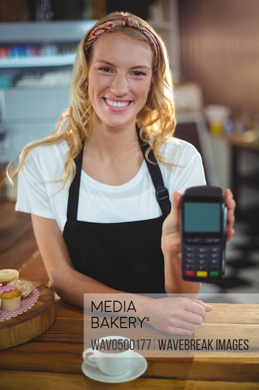 Portrait of smiling waitress holding credit card reader in cafA?