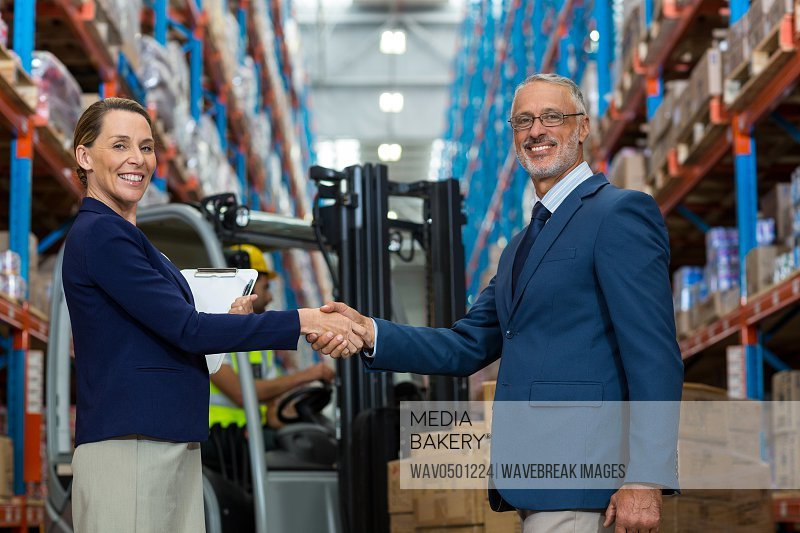 Warehouse manager shaking hands with client in warehouse