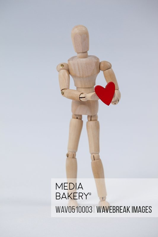 Wooden figurine standing and holding a red heart against white background