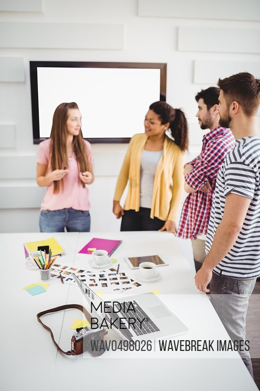 Young editors discussing in meeting at photo editing office