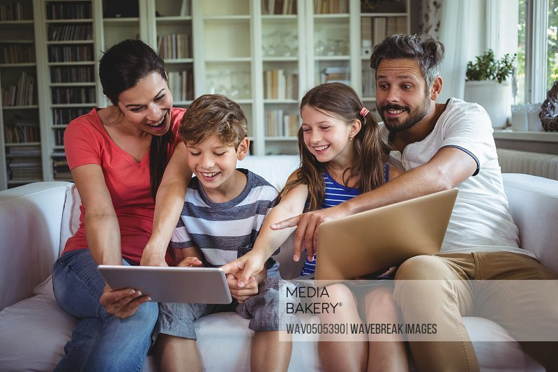 Smiling family sitting on sofa and pointing at digital tablet at home