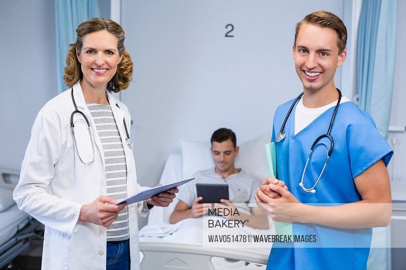 Doctors standing with reports and patient using digital tablet in background