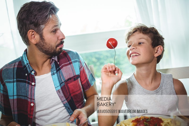 Smiling boy showing a cherry tomato to his father while having meal