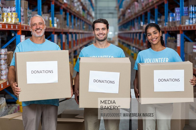 Portrait of three volunteers holding a donations box in the warehouse