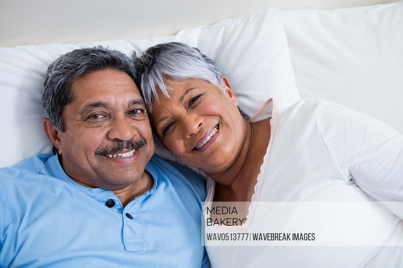 Happy senior couple relaxing on bed in bedroom