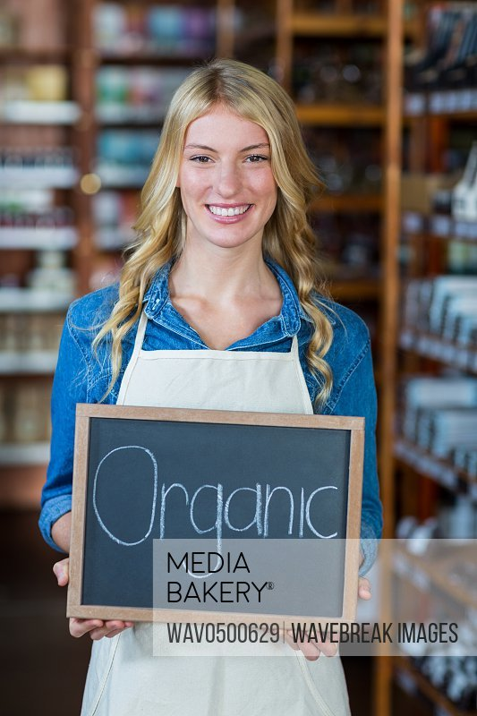 Portrait of smiling female staff holding a organic sign board in supermarket