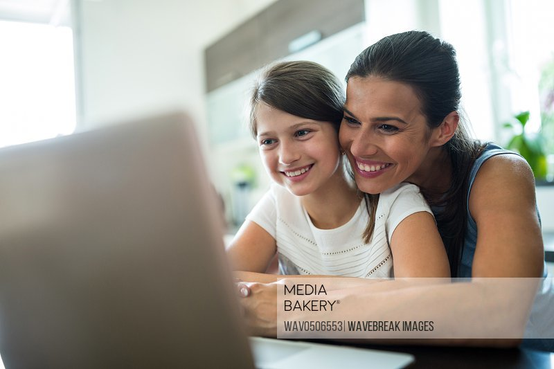 Mother and daughter using laptop and digital tablet in the living room at home
