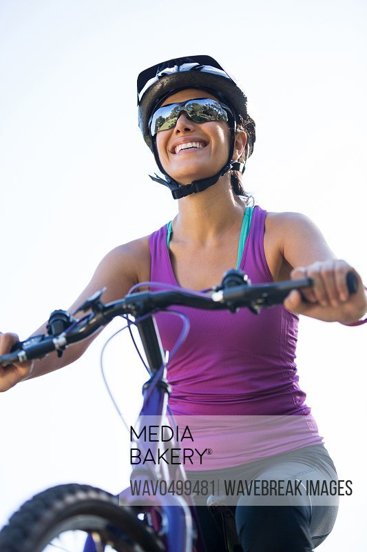 Female cyclist cycling in countryside on sunny day