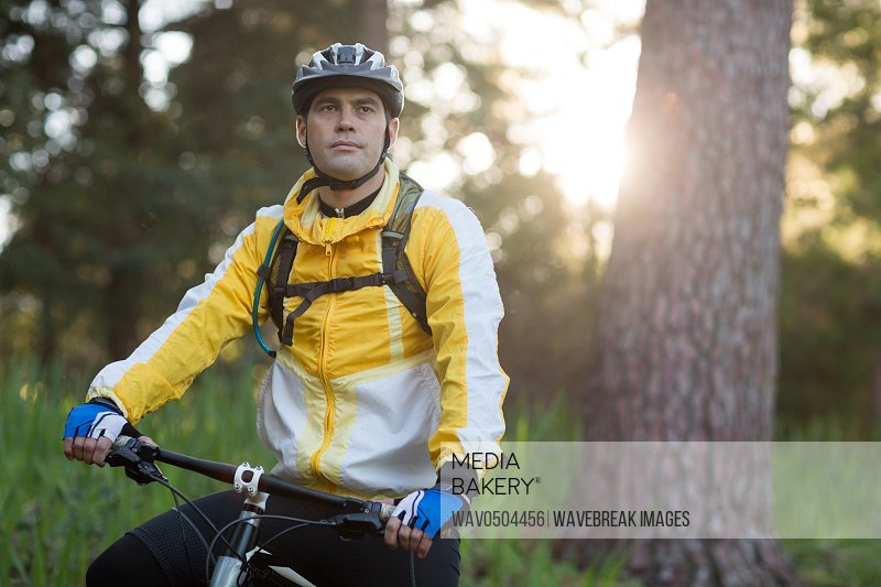 Male biker with mountain bike in countryside forest