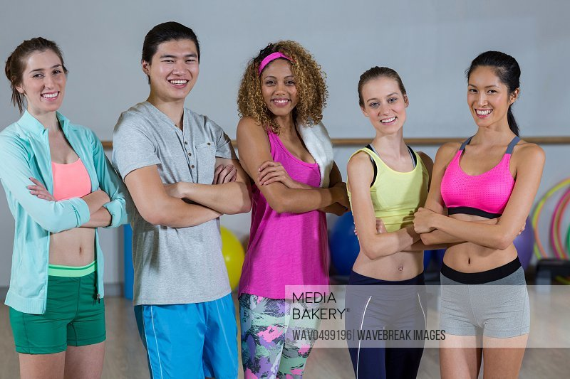 Portrait of group of fitness team standing with arms crossed in fitness studio